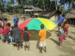 Mukili children play games with the brightly colored parachute.